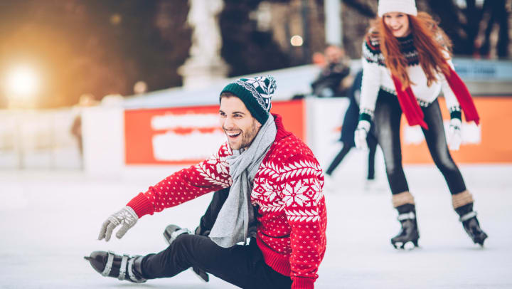 A laughing man in a holiday sweater and skates sits on the ice as a woman skates up from behind him at an outdoor rink.