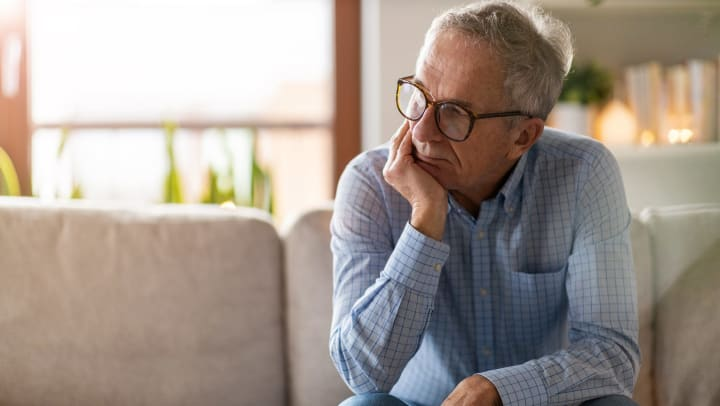 Worried senior sitting alone in his home.