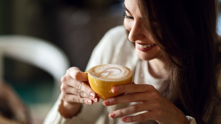 A smiling young woman holds a latte in a mug.