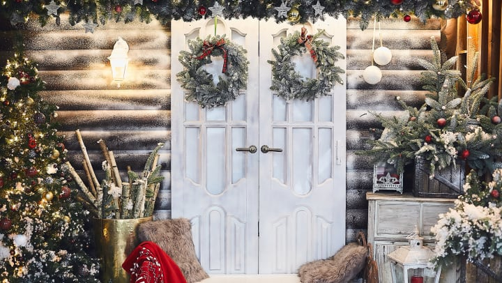 White doors decorated with wreaths and surrounded in a variety of holiday decor, including fake snow, a Christmas tree, a garland, a lantern, and fur cased pillows.