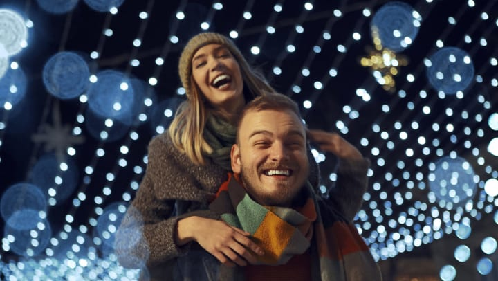 Young couple together for Christmas holidays have fun outside