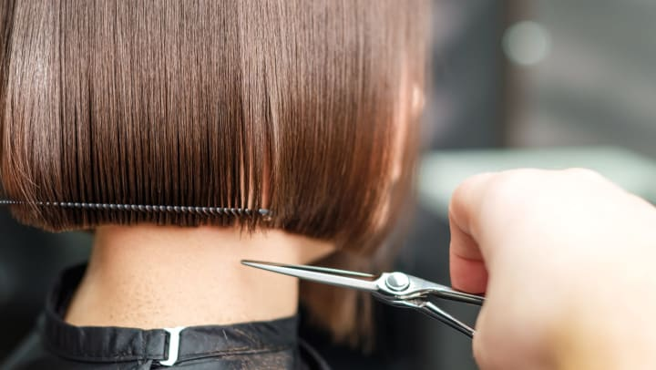 A close-up of a hair stylist's hand holding scissors as they trim a woman's hair.