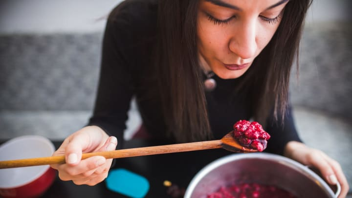 Woman blowing on a spoonful of mashed red berries that she is holding above a half-filled pot.
