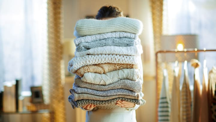 A woman holding a large stack of sweaters in front of her
