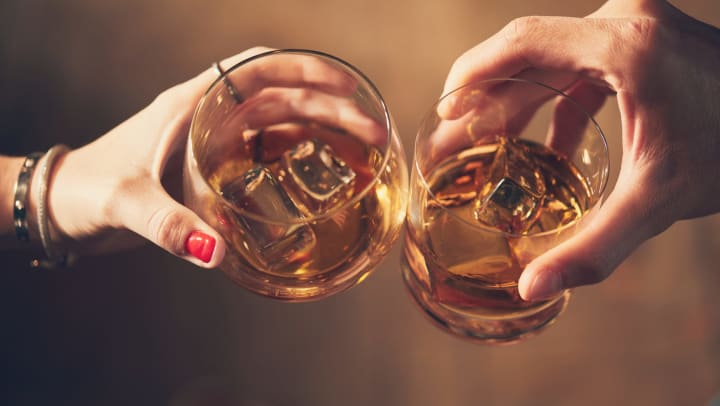 Aerial view of two hands holding glasses filled with a light brown liquid and ice cubes