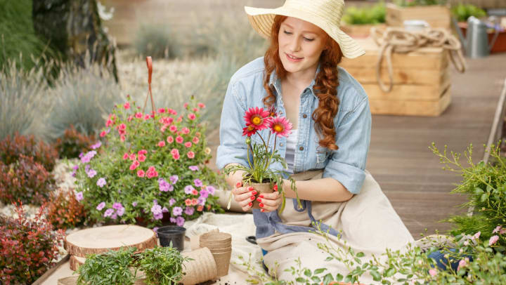A young woman sitting on a deck holds a pot with a flower in it, while surrounded by a variety of other potted plants and flowers.