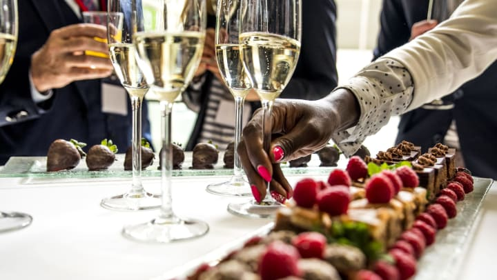 Woman reaching for a champagne glass from a table full of drinks and desserts surrounded by people.