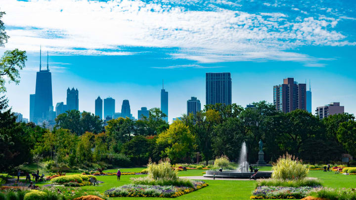 View of a lush green park with a city skyline in the background and a bright blue sky with wispy clouds above