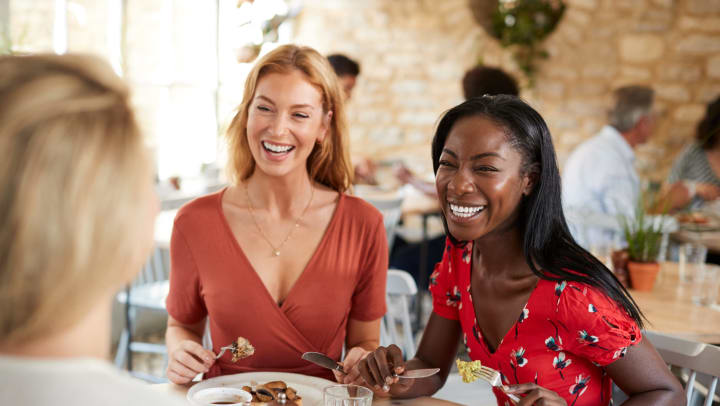 Young female friends smiling at brunch in a cafe.