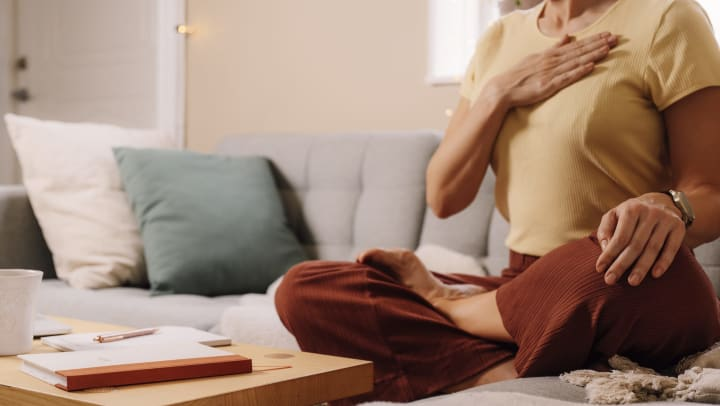 Woman holding a hand to her chest while sitting in a meditative pose on the couch.