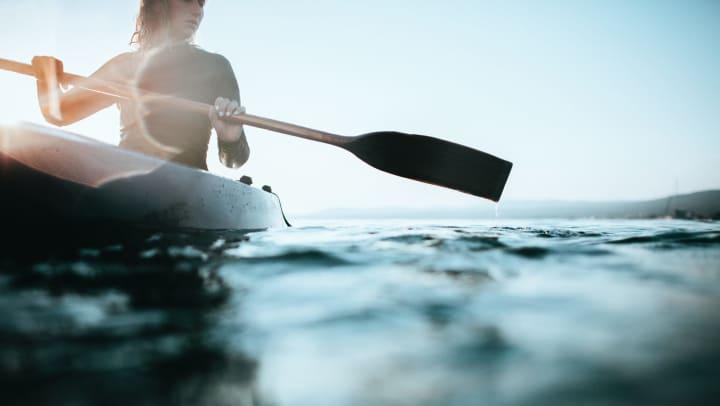 A woman paddling in a canoe in open water