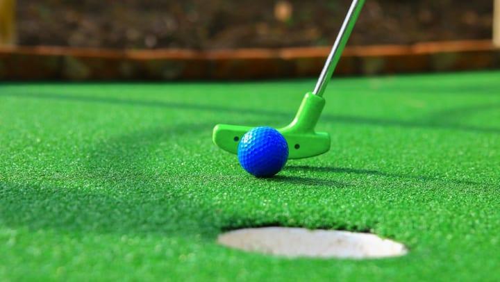 Closeup of green putter hitting blue golf ball toward hole on mini golf course