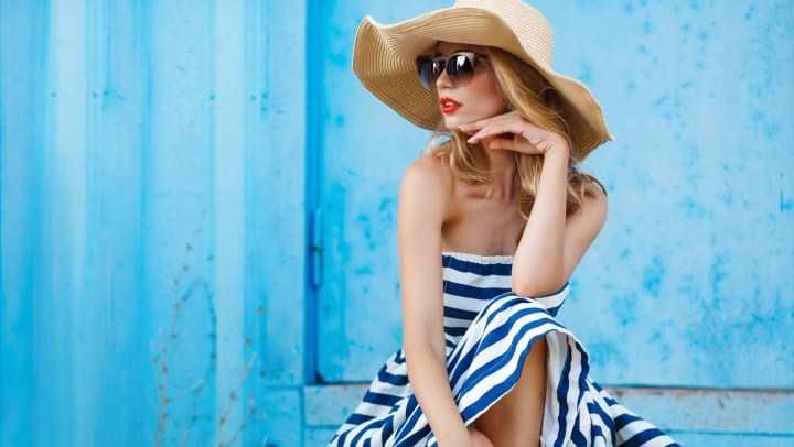 Young woman wearing a white and blue striped dress, sunglasses, and a wide-brim hat, seated in front of a light blue building