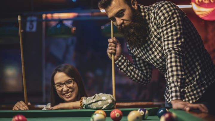 Smiling young man and young woman playing pool in an indoor arcade