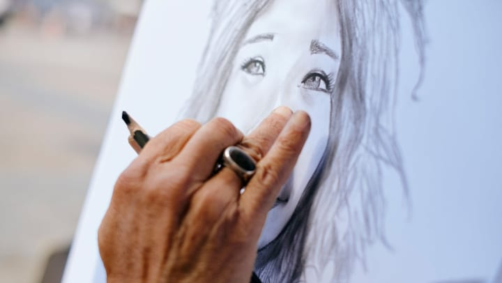 Close-up of an artist's hand as they work on a pencil sketch of a woman's face.