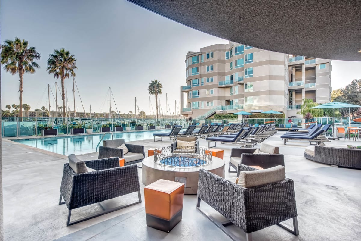 Outdoor kitchen with bar seating and gas barbecue grills at Esprit Marina del Rey in Marina del Rey, California