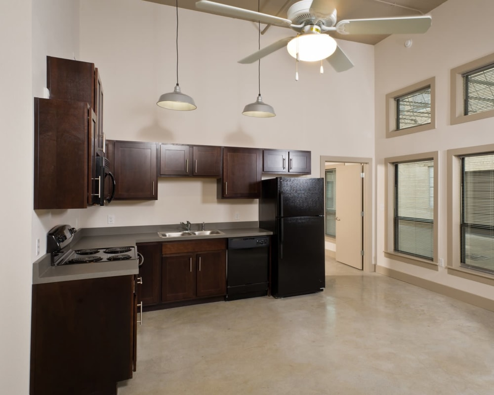 Kitchen with black appliances at Gold Seal Lofts in New Orleans, Louisiana