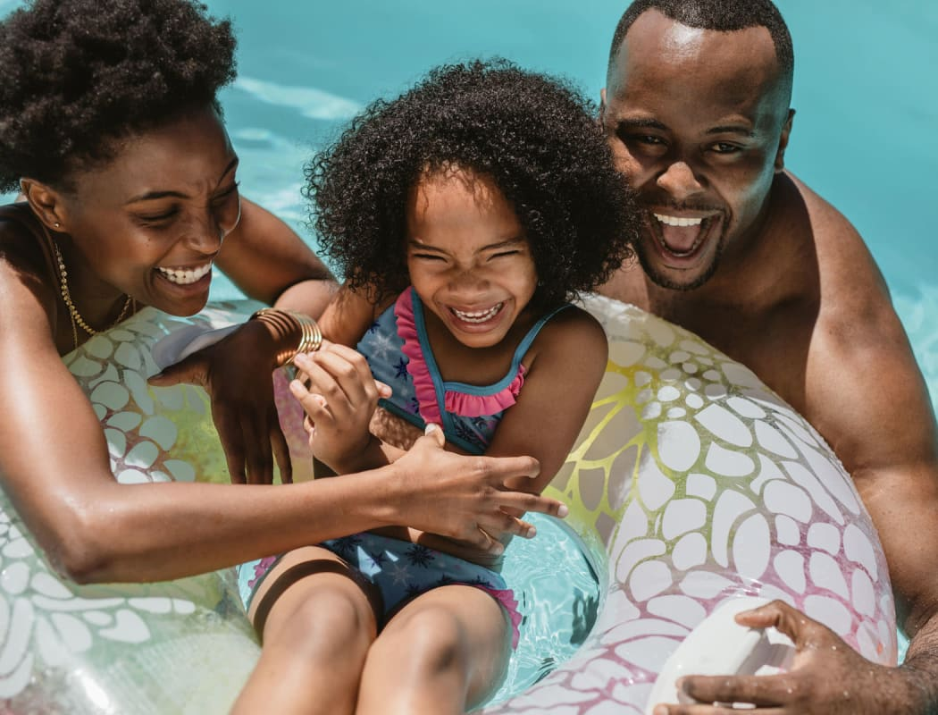 Happy family enjoying a beautiful day in the swimming pool at The Retreat at Arden Village Apartments in Columbia, Tennessee