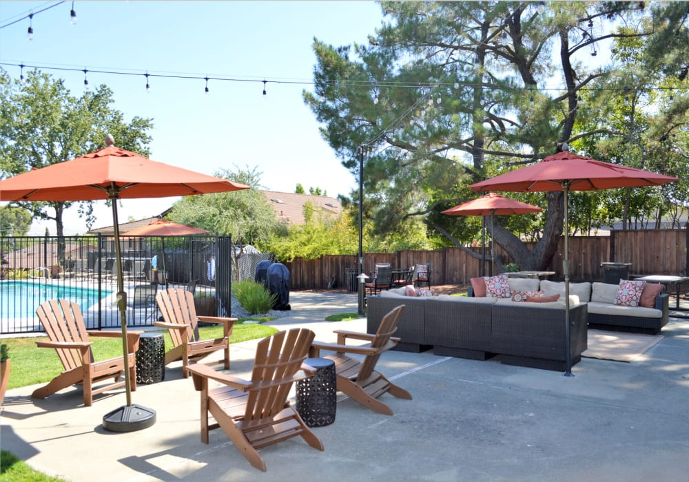 Lounge area with shaded seating near the pool at Pleasanton Heights in Pleasanton, California