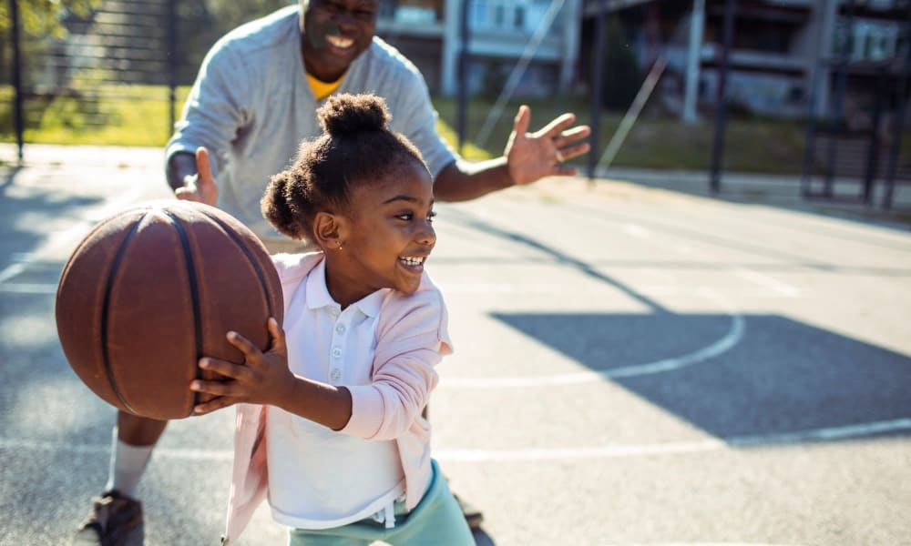 Father and daughter playing a game of basketball at the park near WestEnd At 76Ten in Tampa, Florida