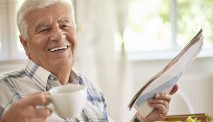 A resident with a cup of coffee and a magazine at The Legacy at Southpointe Drive in Greenville, South Carolina