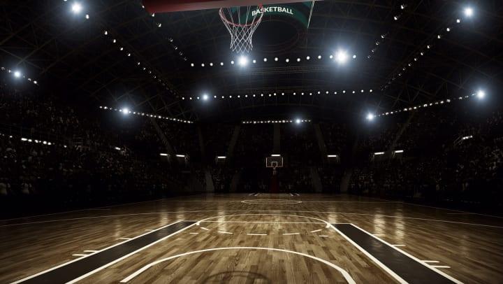 A dimly lit, empty basketball court