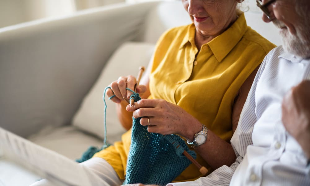 Two residents sitting on a couch, one of them knitting at Governor's Pointe in Mentor, Ohio