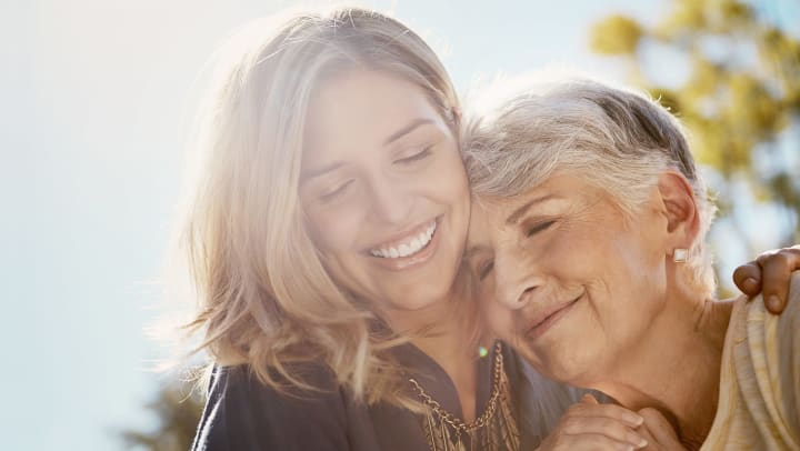 Younger woman with her arm around an older woman, both smiling with their eyes closed.