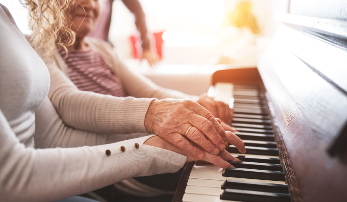 A resident and staff member playing the piano at CERTUS Premier Memory Care Living in Heathrow, Florida.