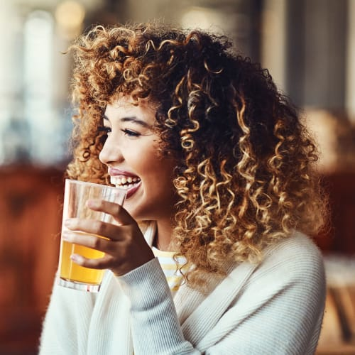A women laughing while enjoying a drink near The Columbia at the Waterfront in Vancouver, Washington
