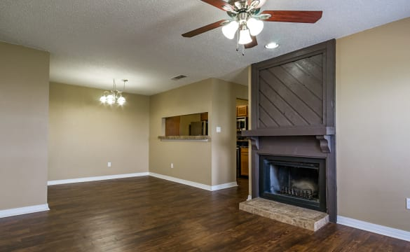 Spacious living area in apartment home at North Pointe Apartments, showcasing ceiling fan, fireplace, and beautiful hardwood floors