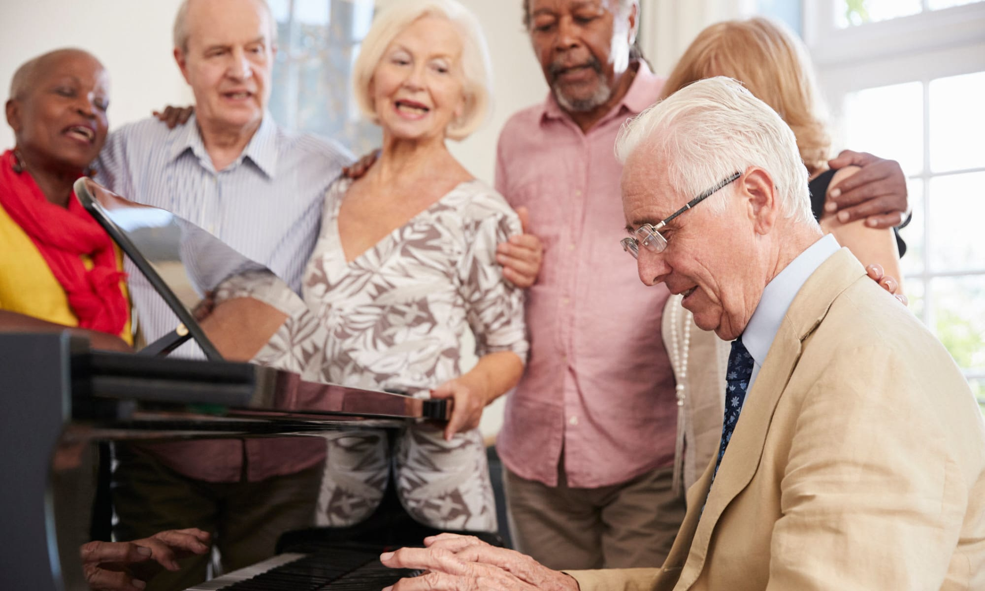 Residents playing the piano and singing at Avenir Memory Care Westside in Los Angeles, California.