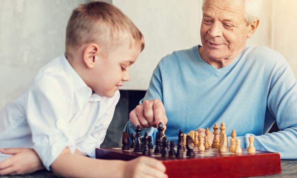 A resident playing chess with a child at Amaran Senior Living in Albuquerque, New Mexico.