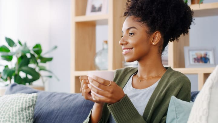 Young woman smiling while holding a mug and sitting on her couch in an organized home
