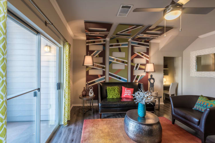 Well-decorated living room with a ceiling fan in a model home at Sage at 1825 Apartments in Pflugerville, Texas