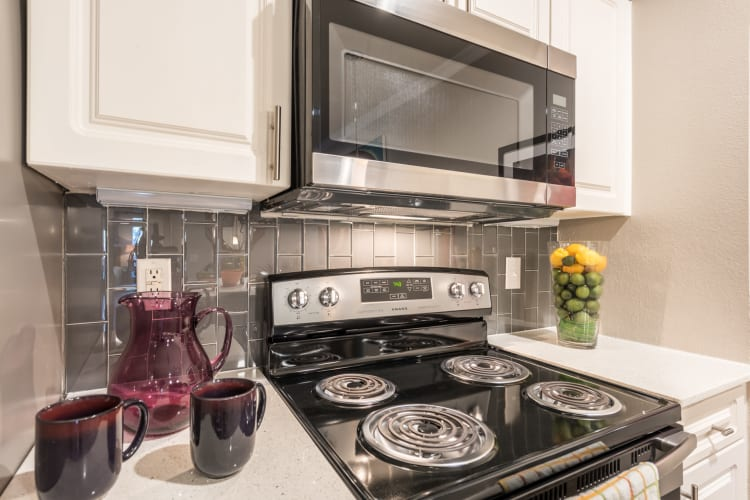 Beautiful kitchen counter tops with a tile back splash at Sage at 1825 Apartments in Pflugerville, Texas