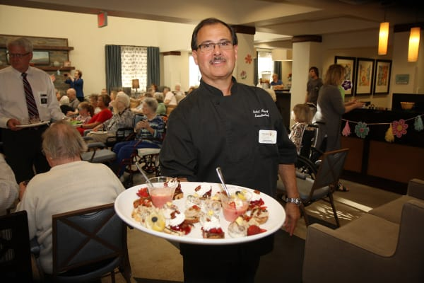 Our chef Robert holds dining table at Prairie House Assisted Living and Memory Care in Broken Arrow, Oklahoma
