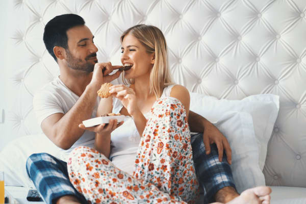 A couple enjoying a meal in bed at Hunt Club Apartments in Cockeysville, Maryland