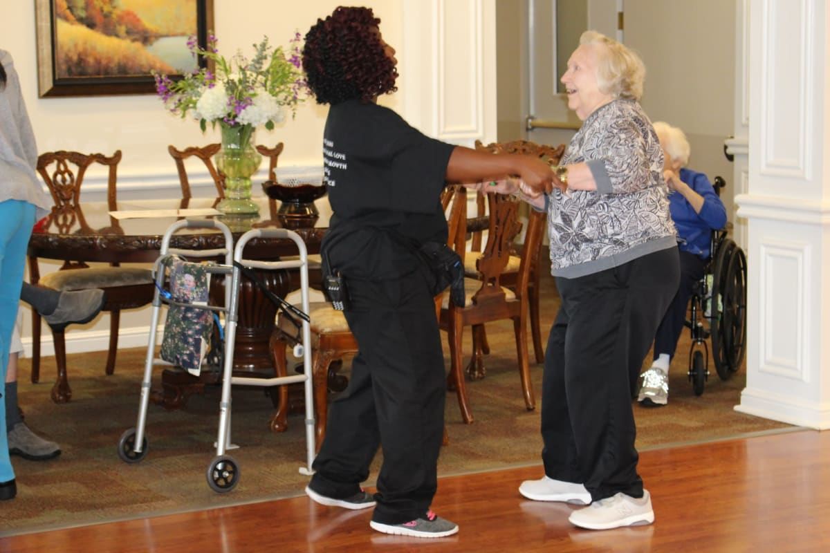 Resident dancing with care worker at Parsons House Frisco in Frisco, Texas