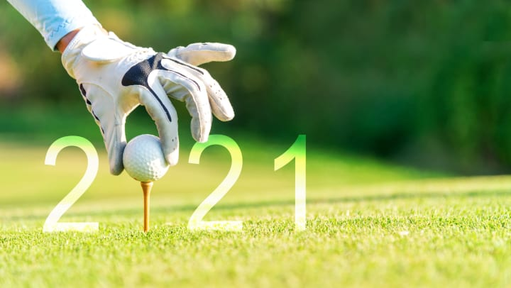 A gloved hand placing a golf ball on a golf tee. The golf ball standing in for the 0 in a 2021 silhouette