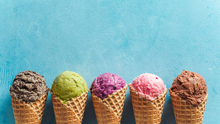 Different flavored ice cream cones against a blue background.
