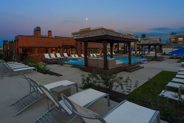 Lounge chairs next to cabana and beautiful pools at Palmer House Apartment Homes in New Albany, Ohio