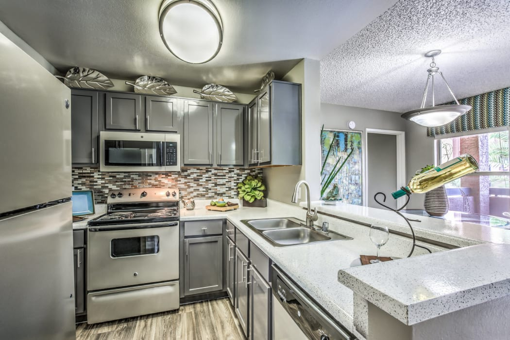 Modern kitchen with gray cabinetry and granite countertops in a model home at Solis at Flamingo in Las Vegas, Nevada