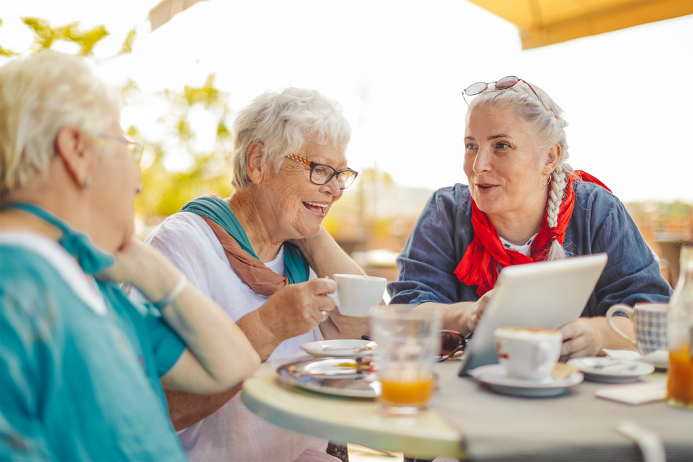 Group of residents sitting outside having lunch at Sunstone Village in Denton, Texas