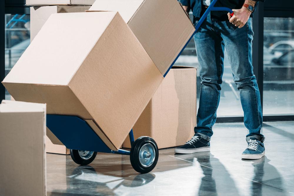 Man pushing dolly loaded with boxes at A-American Self Storage in Santa Barbara, California
