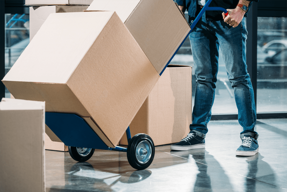 Man pushing dolly loaded with boxes at A-American Self Storage in Rialto, California