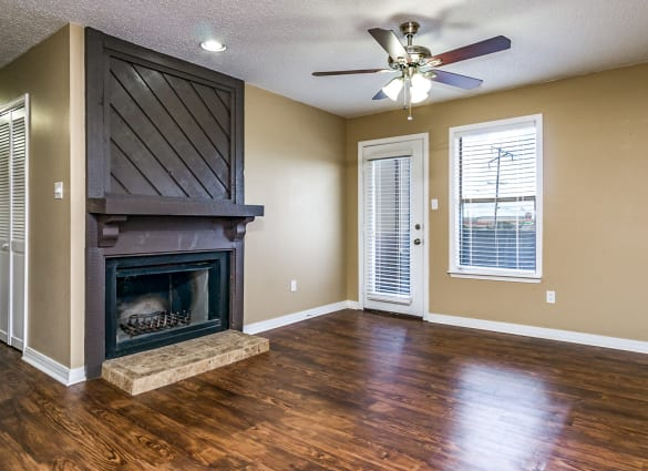 Interior view of apartment home living room with ceiling fan, hardwood floors, and fireplace at North Pointe Apartments