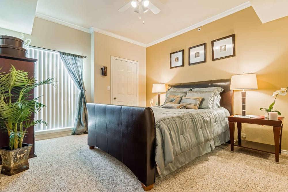 Luxurious carpeting and a ceiling fan in the well-furnished master bedroom of a model home at Vail Quarters in Dallas, Texas