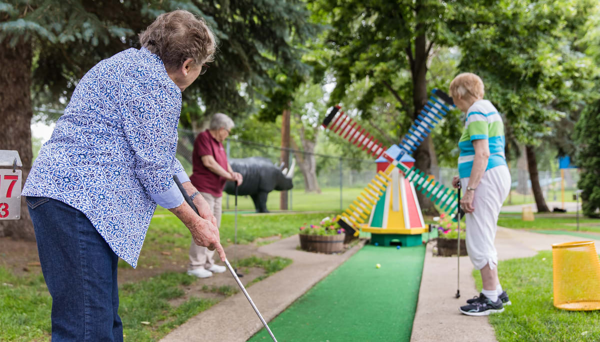 senior residents playing miniature golf