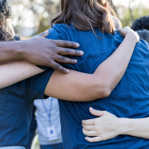 People embracing during charitable work that Olivenhain Self Storage takes part in